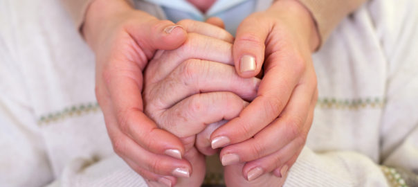 Senior and caregiver holding hands